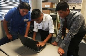 Johnnie Iron CLoud, Ardine Gentilezo and Derrick Meno work on their presentation for the SUnpower Solar Energy Academy at the Lemoore Middle College High School on Friday afternoon.